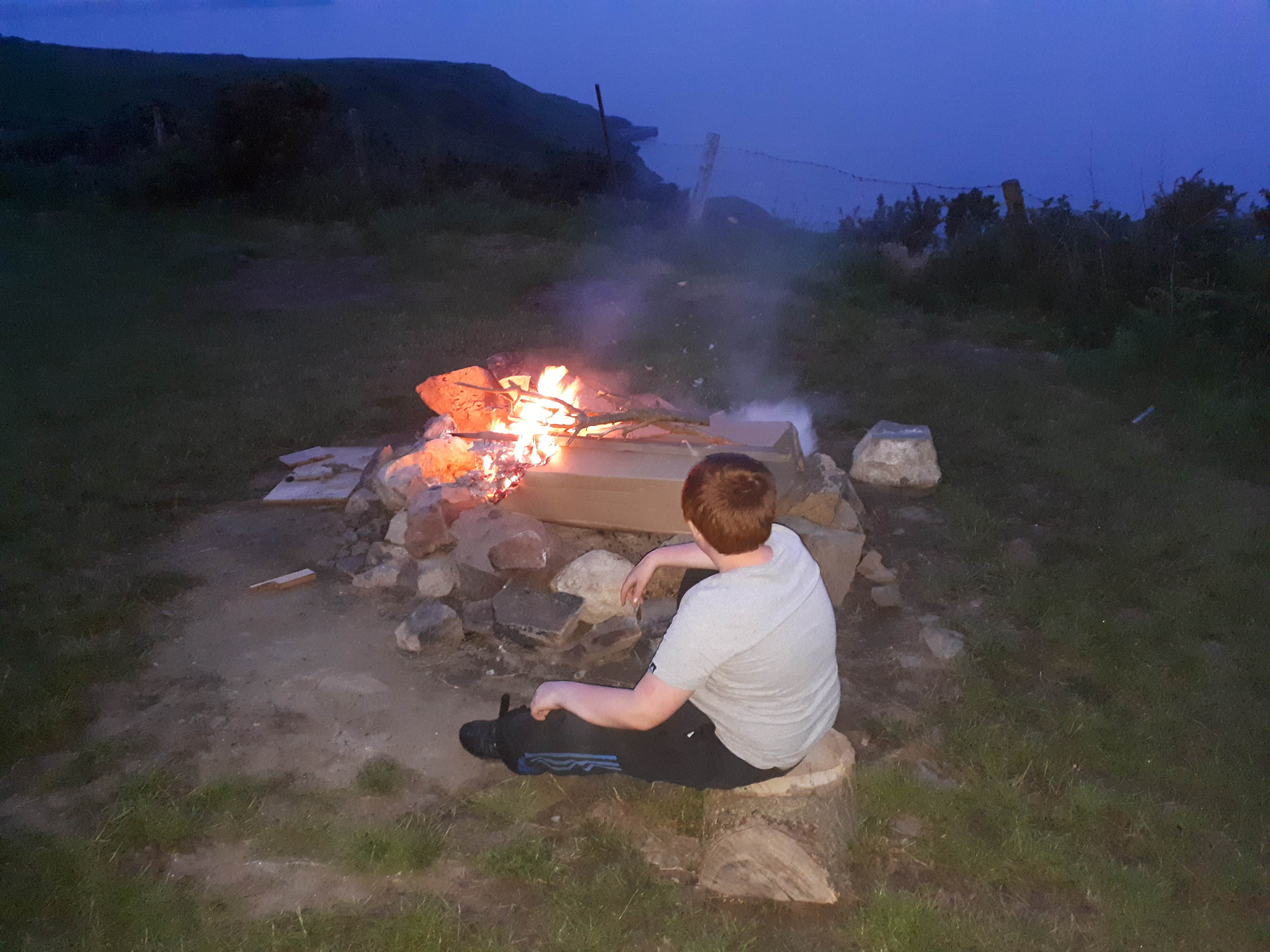 A picture of a boy enjoying a campfire at Penisarlon farm
