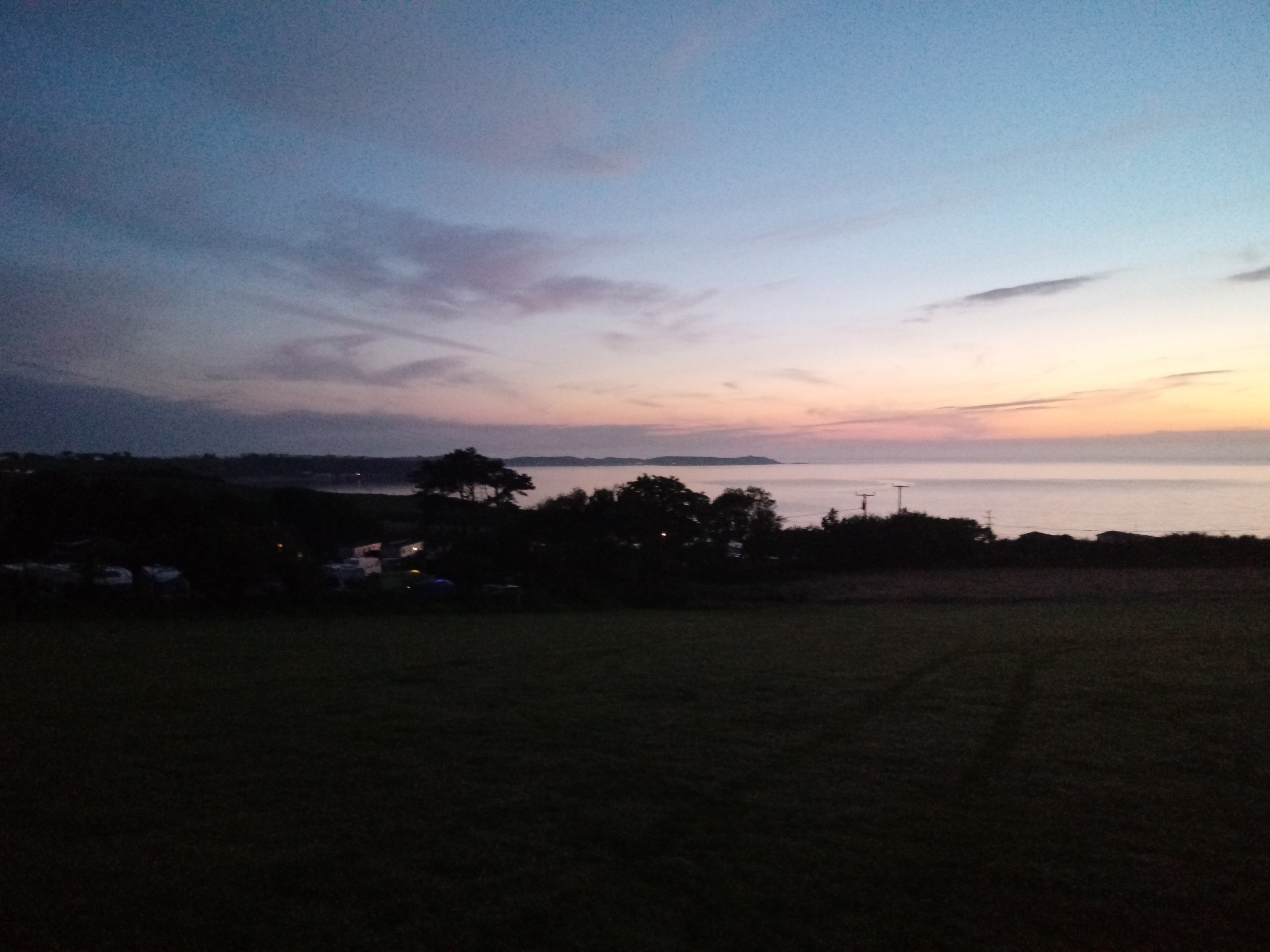The image is a picture of the campsite during the evening time, looking out over the campsite you can see the sea in the distance as well as Morfa Nefyn