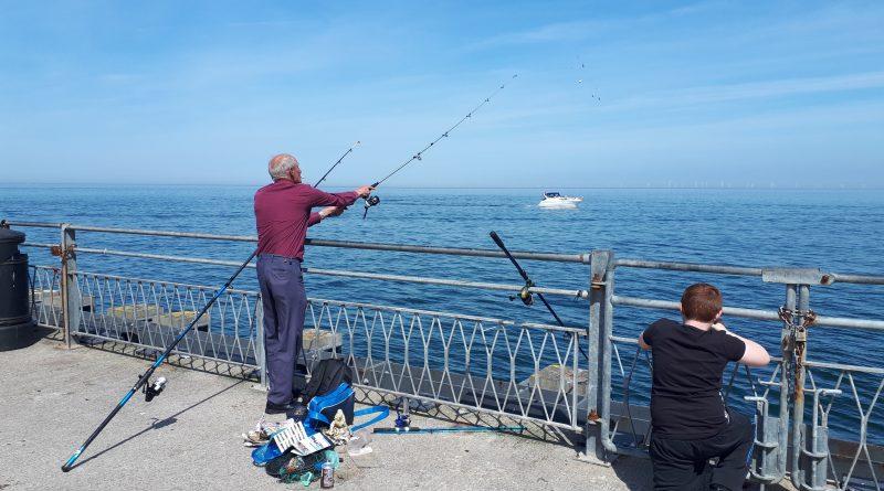 A man and boy fishing from Llandudno Pier