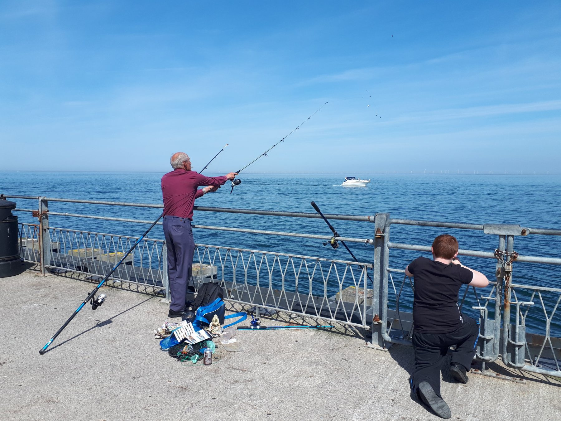 A man and boy fishing from Llandudno Pier